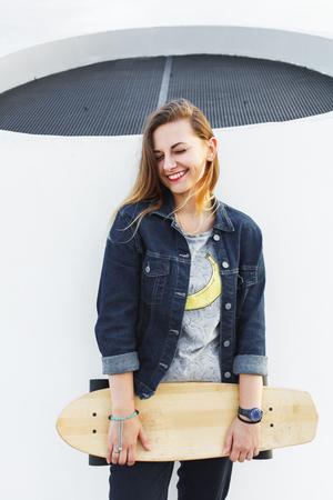 Portret van een jong gelukkig hipstermeisje met longboard in haar handen