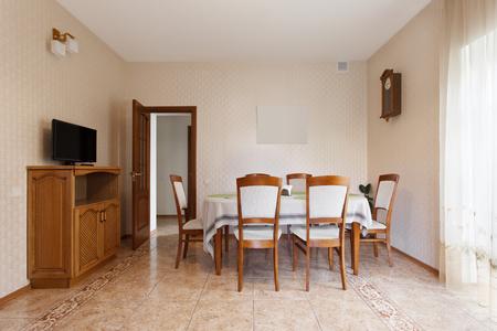 Eetkamer met houten tafel en stoelen in het herenhuis