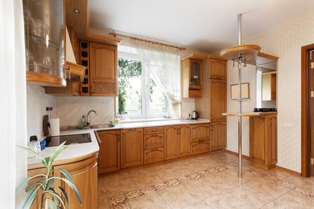 Keuken met houten kasten en een ontbijtbar in het herenhuis