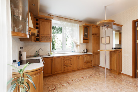 Kitchen with wooden cupboards and a breakfast bar in the mansion Stock Photo