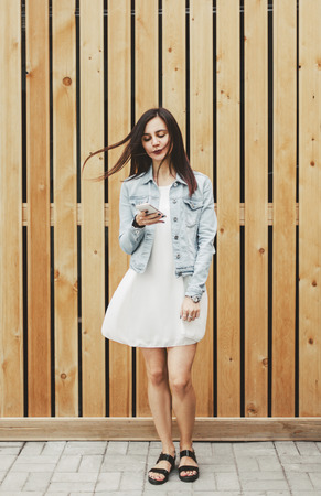 Beautiful girl standing with a smartphone in hand and reading posts on social networks Stock Photo