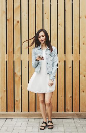 Mooi meisje die zich met een in hand smartphone bevinden en posten op sociale netwerken lezen