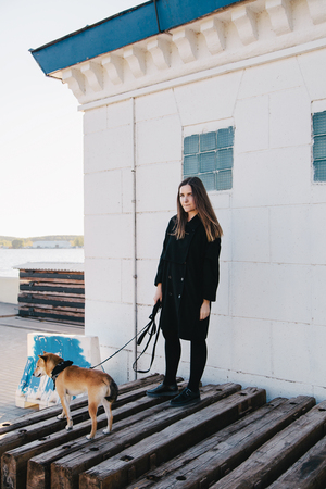 Young beautiful girl in a black clothes holding a red dog on a leash
