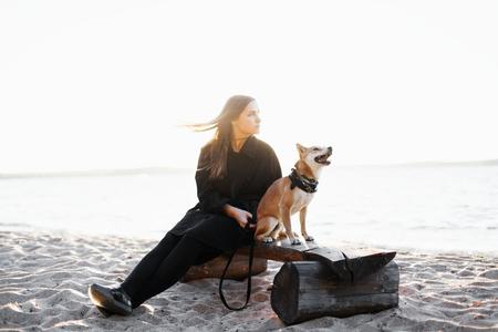 Het jonge donkerbruine meisje in een zwarte kleding zit op het strand van het overzees met de rode hond van Japan. Focus op de hond