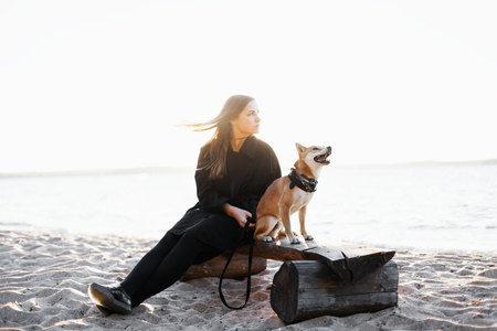 Young brunette girl in a black clothing sits on the beach of the sea with japan red dog. Focus on the dog