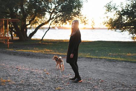 Jonge mooie vrouw in zwarte kleding lopen met een rode hond in een leiband dichtbij de vijver Stockfoto
