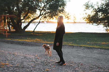 Young beautiful woman in black clothes walking with a red dog on a leash near the pond