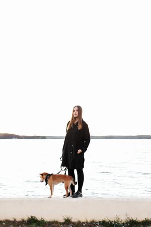 Jong mooi meisje in zwarte kleding die met een rode Japanse hond staat op een leiband dichtbij de vijver Stockfoto