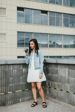 Jonge aantrekkelijke brunette vrouw met een glas koffie in een stedelijke omgeving