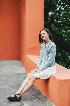 Jong mooi lachend meisje in een witte jurk in de stedelijke omgeving