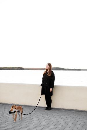 Jong mooi meisje in zwarte kleding die met een rode Japanse hond loopt op een leiband dichtbij de vijver
