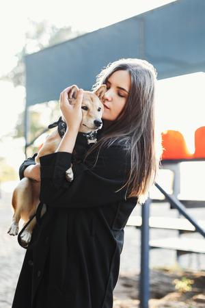 Portret mooi meisje in een zwarte kleding die een hond in openlucht houdt