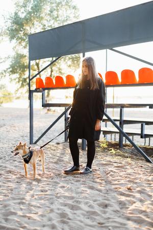 Mooi jong meisje dat met een Japanse hond op het strand loopt op een zonnige dag in de herfst