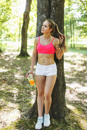 Beautiful young girl in a bright athletic short top with glass of fresh orange juice