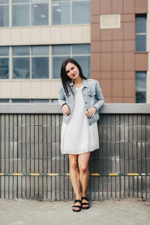Jonge aantrekkelijke brunette vrouw in een witte jurk in de stedelijke omgeving Stockfoto