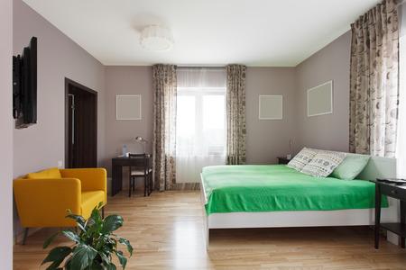 Grote moderne slaapkamer in groene en gele kleuren met kleine werkplek