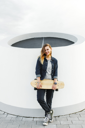 Smiling hipster girl with longboard in her hands in urban environment