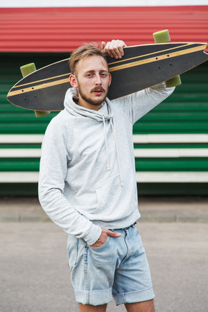 Sexy hipster man standing with longboard on his shoulder