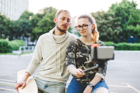 Young married couple with longboards making photo using selfie stick
