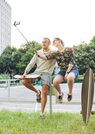 Young couple with longboards making photo using selfie stick