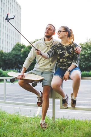 Two young people with longboards making photo using selfie stick Stock Photo