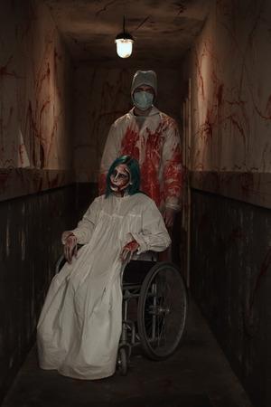 Verschrikking. Verschrikkelijk zombie meisje zit in een rolstoel en een dokter in een verlaten ziekenhuis. Halloween