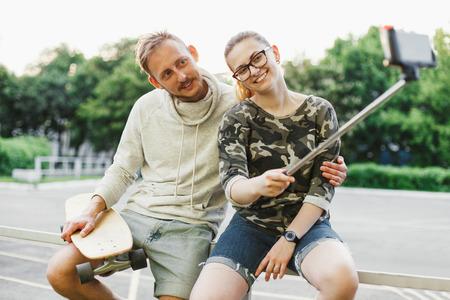 Twee jonge vrienden met longboards foto met behulp van selfie stok