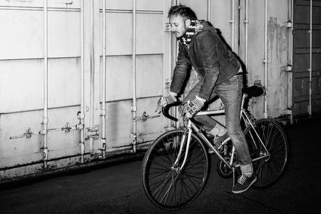 Portret van een vrolijke mannelijke hipster op vaste-gear fiets. Zwart-wit portret