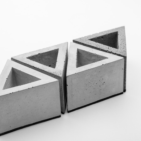 Several triangular pots of decorative concrete on a white background