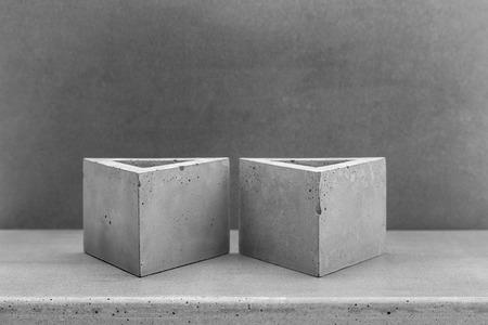 Driehoekige plantenbakken gemaakt van natuurlijke beton op concrete achtergrond Stockfoto