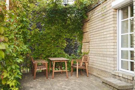 Gezellig terras van een landhuis met klimop overgroeid Stockfoto