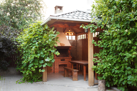 Gezellig houten gazebo met een grill en een tafel buitenshuis