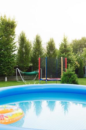 Comfortabele zithoek van een landhuis met een groen gazon en een trampoline