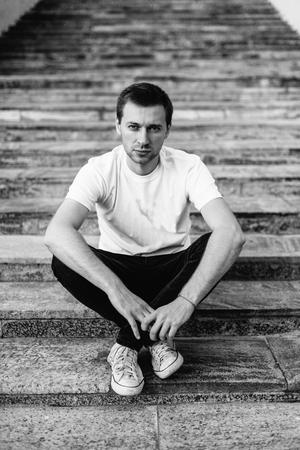 Portret van verdrietige jonge man zittend op de trappen. Zwart-wit portret van een man