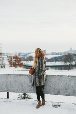 Eenzaam meisje bewondert de stad buiten op een winterdag