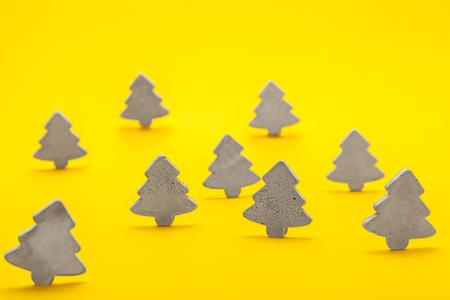 Decoratieve Kerstbomen van betonstand op een gele achtergrond