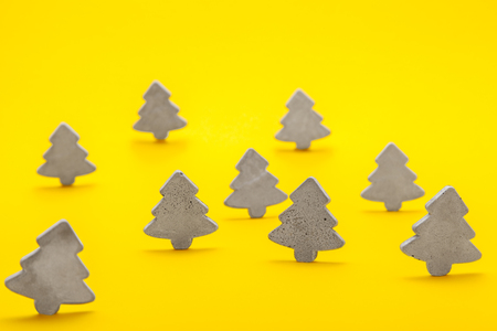 Decorative Christmas trees of concrete stand on a yellow background