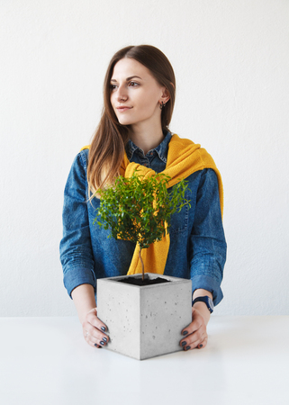 Portrait of a beautiful girl with a houseplant in a concrete pot Stock Photo