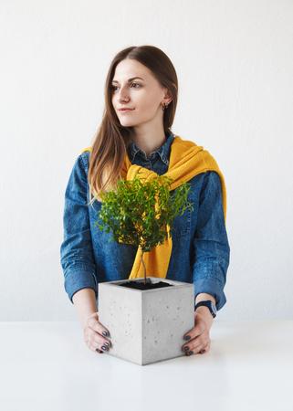 Portret van een mooi meisje met een houseplant in een betonnen pot Stockfoto