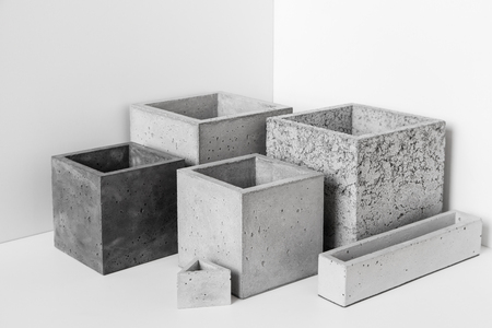 Pots of different shapes of concrete for houseplants stand on the table in the room