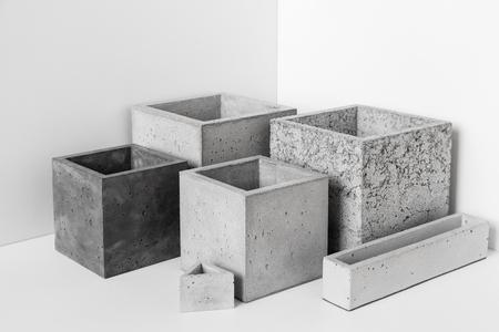 Potten van verschillende vormen van beton voor kamerplanten staan op de tafel in de kamer