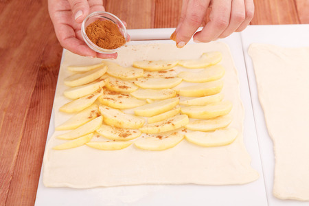 Cooking apple pie. Cook puts apple slices on the dough and sprinkle them with cinnamon