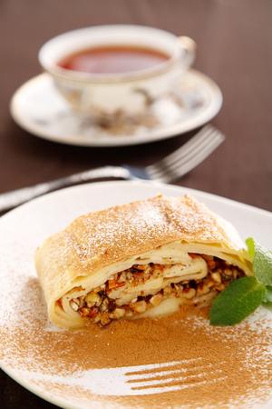 The dessert on the table. A piece of delicious nut roll and a Cup of tea is on the dining table. Stock Photo