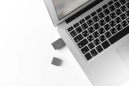 USB memory stick made of concrete on a laptop. Brutal USB flash drive of the cement of hand made 스톡 콘텐츠