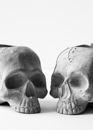 Two gray concrete human skulls on white background. A skull made of cement for home decor Stock Photo