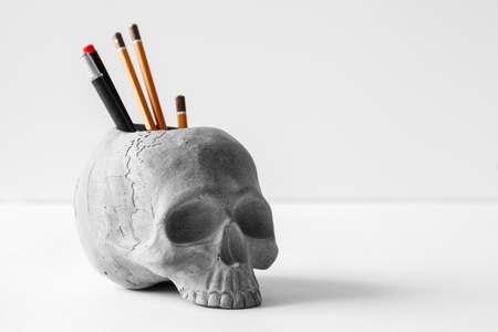 The concrete organizer in the office.Holder for writing instruments made of concrete in the form of a human skull on white background