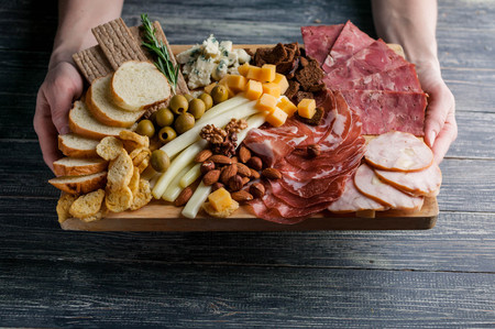 Assorted from meat and cheese on a chopping board. Smoked sausage, meat roll from a turkey with cheese, jamon, olives, nuts and various grades of cheese. Фото со стока