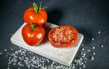 Tomatoes and salt on a dark background. Low-key lighting
