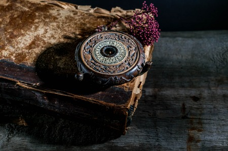 Old Oriental Feng Shui compass on a background of an old book. Wabi Sabi Concept Stock fotó