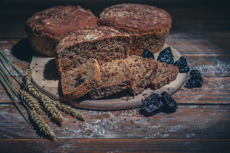 Rye bread with flax seeds and prunes on a wooden background. Homemade baking. Low key lighting. Light toning